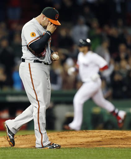 Baltimore Orioles' Tommy Hunter rubs his face as Boston Red Sox's Jarrod Saltalamacchia rounds third base on a solo home run in the sixth inning of a baseball game in Boston, Wednesday, April 10, 2013. (AP Photo/Michael Dwyer)