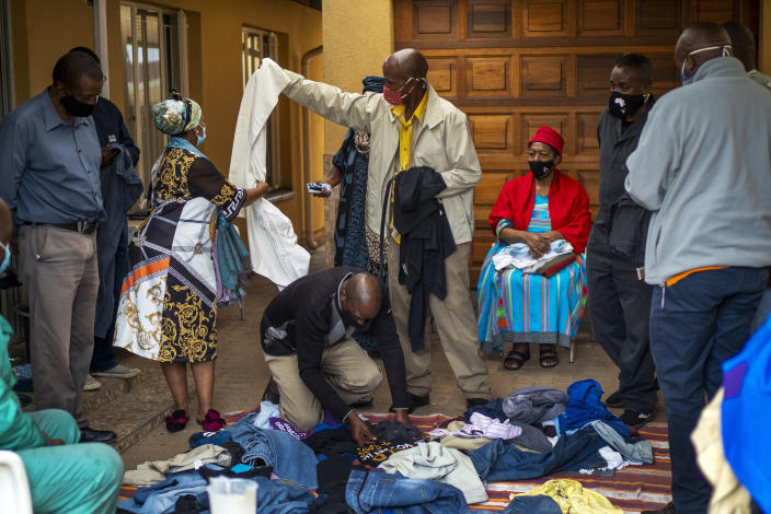 FILE - In this Nov. 21, 2020, file photo, family members select clothes that belonged to Benedict Sami Vilakazi, who died of COVID-19, during an Ukugeza cleansing ceremony at Vilakazi's home in Soweto, South Africa. Africa has surpassed 100,000 confirmed deaths from COVID-19 as the continent praised for its early response to the pandemic now struggles with a dangerous resurgence and medical oxygen often runs desperately short. (AP Photo/Jerome Delay, File)