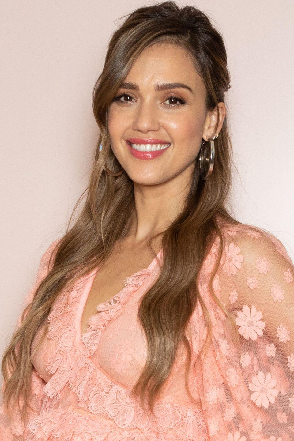 <p>Jessica Alba wears her beach waves in a relaxed look with a side part. The style is the perfect frame for a pair of statement earrings.</p>