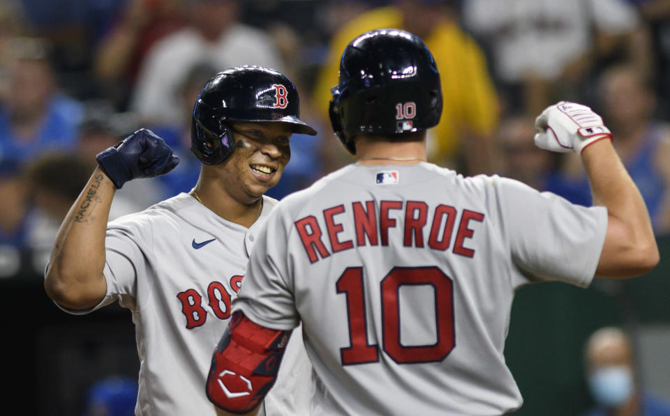 Boston Red Sox's Rafael Devers, left, is congratulated by teammate Hunter Renfroe after hitting a home run during the eighth inning of a baseball game against the Kansas City Royals in Kansas City, Mo., Friday, June 18, 2021. (AP Photo/Reed Hoffmann)