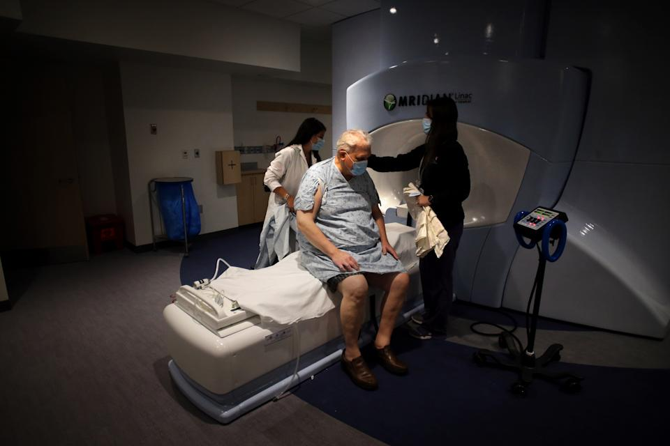 BOSTON, MA - JUNE 10: Radiation therapists Jessica Penney, left, and Jennifer Campbell, right, prepare cancer patient Kenton Fabrick for his treatment in the Radiation Oncology Department at Brigham and Women's Hospital in Boston, MA on on June 10, 2020. (Photo by Craig F. Walker/The Boston Globe via Getty Images)