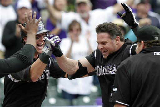 Colorado Rockies pinch hitter Jason Giambi, right, steps on home plate while being congratulated by Troy Tulowitzki, left, after hitting a walk-off home run off Los Angeles Dodgers relief pitcher Scott Elbert during the ninth inning of a baseball game, Wednesday, May 2, 2012, in Denver. The Rockies won 8-5. (AP Photo/Barry Gutierrez)