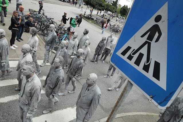 <p>Performance artists covered in clay to look like zombies walk over a crosswalk trance-like through the city center on July 5, 2017 in Hamburg, Germany. (Friedemann Vogel/Getty Images) </p>