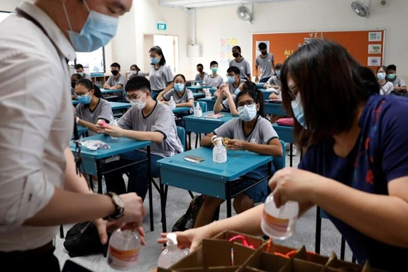 Hand sanitisers are distributed to students in class at Yio Chu Kang Secondary School, as schools reopen amid the coronavirus disease (COVID-19) outbreak in Singapore June 2, 2020. REUTERS/Edgar Su