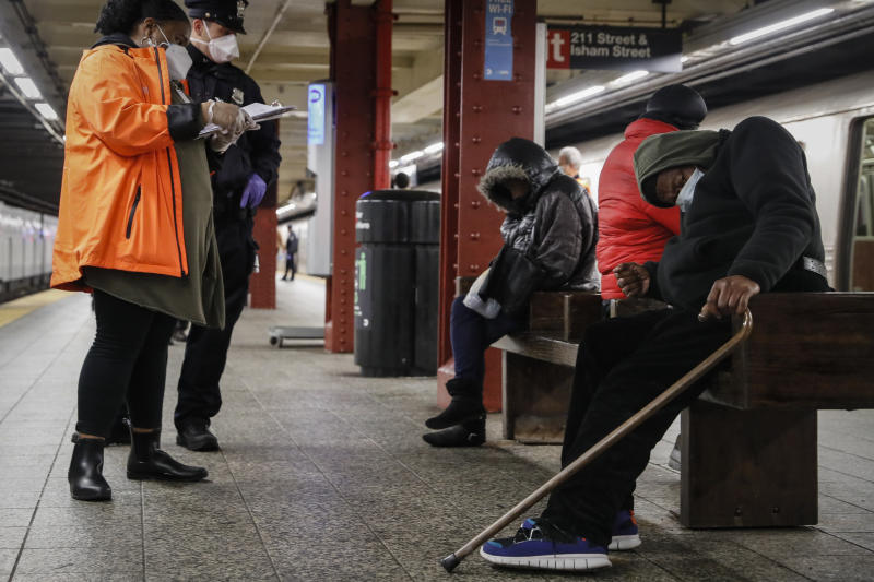 FILE - In this April 30, 2020 file photo, homeless outreach personnel assist passengers found sleeping on subway cars at the 207th Street A-train station in the Manhattan borough of New York. New York City transit officials said they're providing buses for homeless people to shelter from unseasonably frigid temperatures this weekend during newly instituted overnight subway closures. The subway system has been shutting down from 1 to 5 a.m. since Wednesday, May 6,  as part of an outbreak-related plan for daily train disinfecting.  (AP Photo/John Minchillo, File)
