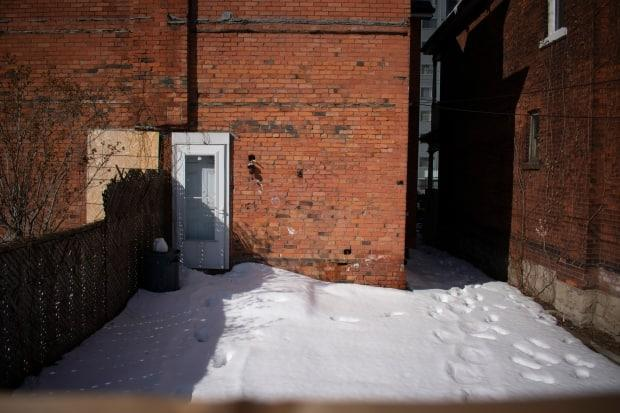 The backyard of 104 has footprints while the back door of 102 Wellington Street North is boarded up.