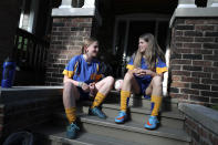 Ruby Wood, left, and her twin sister, Lola, talk on their home stoop in Toronto, Canada, on Monday, July 12, 2021. With Lola's aversion to needles, their mother told her: If you get the vaccine you'll be able to see your friends again. You'll be able to play sports. And enticed by the promise of resuming a normal, teen life, Lola agreed. (AP Photo/Kamran Jebreili)