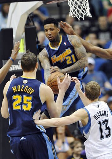 Denver Nuggets' Wilson Chandler (21) goes high to pass to Timofey Mozgov of Russia, left, as Luke Ridnour, right, of Minnesota defends defends in the first half of an NBA basketball game Sunday, March 25, 2012, in Minneapolis. (AP Photo/ Jim Mone)