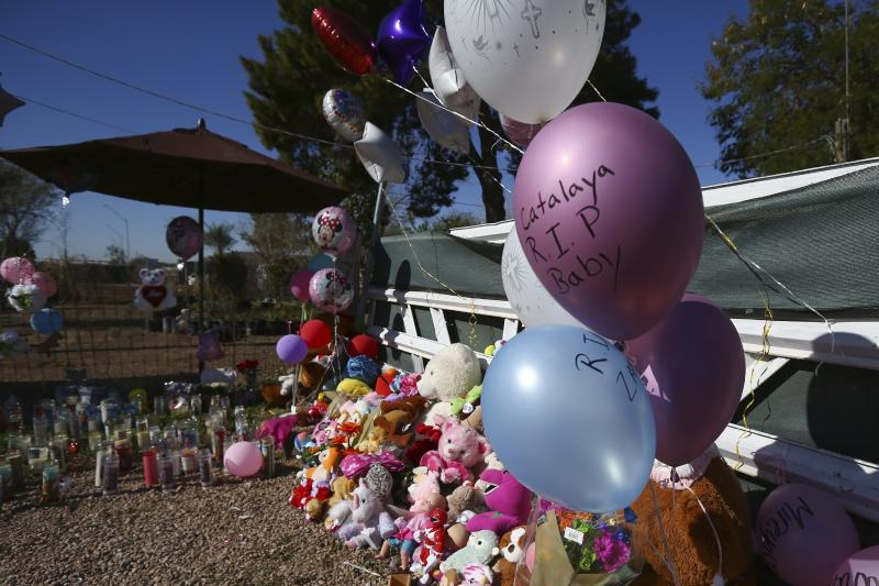 A makeshift memorial grows in front of the home where Rachel Henry was arrested on suspicion of killing her three children after they were found dead inside the family home earlier in the week, shown here Thursday, Jan. 23, 2020, in Phoenix. (AP Photo/Ross D. Franklin)