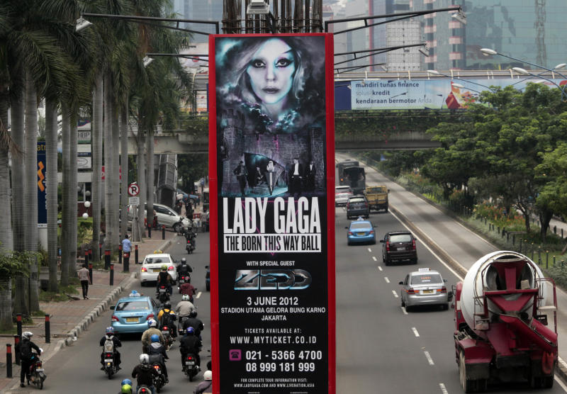 Motorists ride past a promotional banner for US singer Lady Gaga's Born This Way Ball Asia Tour in Jakarta, Indonesia, Tuesday, May 15, 2012. Lady Gaga might have to cancel her sold-out show in Indonesia because police worry her sexy clothes and dance moves undermine Islamic values and will corrupt the country's youth. (AP Photo/Dita Alangkara)