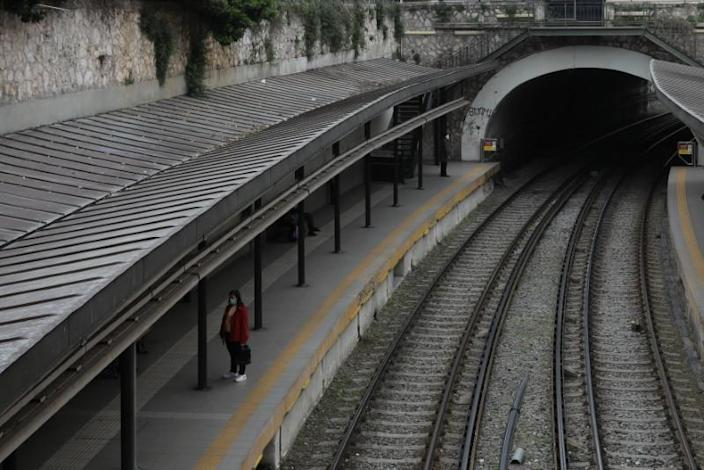 A passenger wearing a protective face mask waits at an almost empty train station, following an outbreak of the coronavirus disease (COVID-19), in Athens