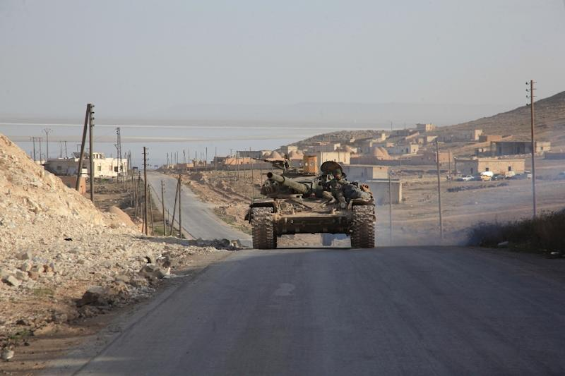 Syrian government forces drive a tank on a road during a military operation against the Islamic State (IS) group in the villages of Zarour and Khanaser, in the Aleppo governorate, on February 26, 2016