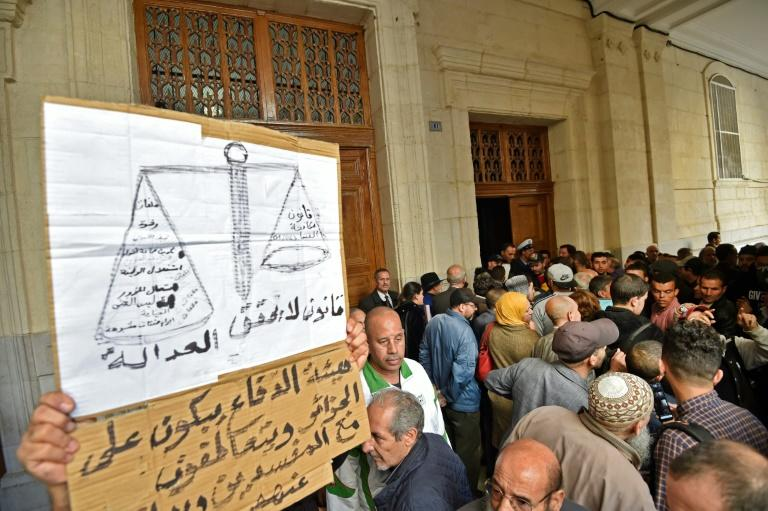 Algerians gather at the entrance of the Sidi M'hamed court in Algiers ahead of the start of a corruption trial for former political leaders and business tycoons