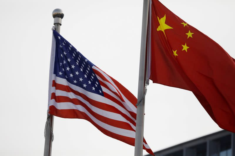 FILE PHOTO: Chinese and U.S. flags flutter outside the building of an American company in Beijing