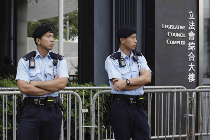 Police stand guard at fencing surrounding the Legislative Council to help block protesters during upcoming meetings on the government's extradition law bill, in Hong Kong, Tuesday, June 11, 2019. Local media reports said police were mobilizing thousands of additional officers to keep order amid calls for protesters to begin gathering Tuesday night. Some businesses have also announced plans to close on Wednesday and scattered reports told of students planning to boycott classes. (AP Photo/Vincent Yu)