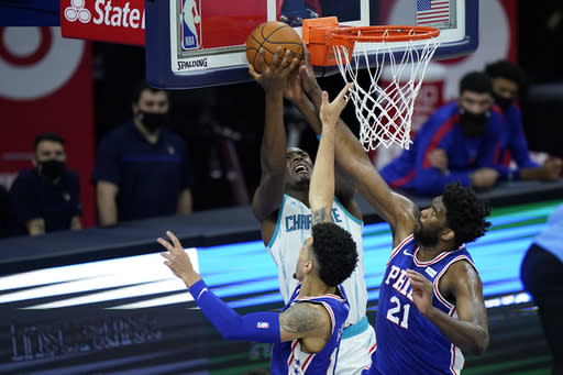 Charlotte Hornets' Bismack Biyombo, left, goes up for a shot against Philadelphia 76ers' Joel Embiid, right, and Danny Green during the second half of an NBA basketball game, Monday, Jan. 4, 2021, in Philadelphia. (AP Photo/Matt Slocum)