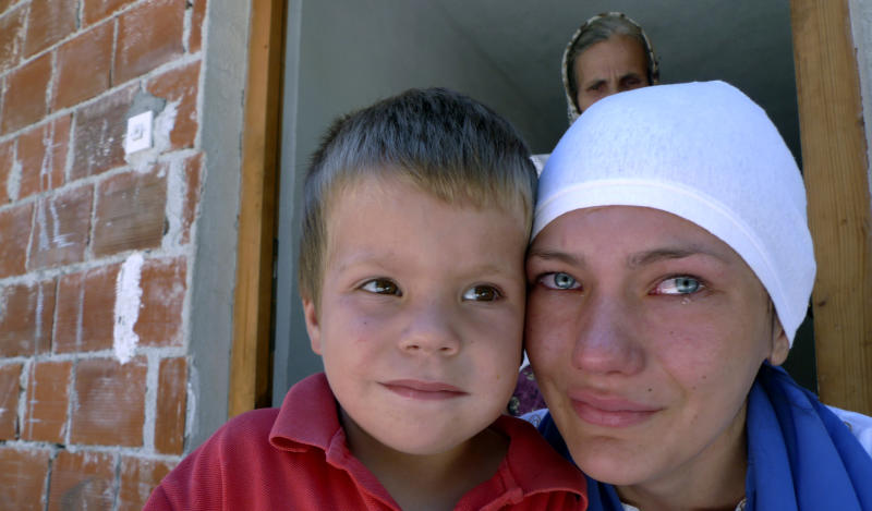 In this Saturday Aug. 11, 2012 photo Fehima Busevac, right, and Bakir Bijelic, the aunt and brother of 6-year-old Tarik Bijelic cry on the doorstep of their small house in the village of Olovske Luke, 60 kilometers north of Sarajevo, Bosnia. Tarik Bijelic was hit by a land mine last week as he scavenged in the forest for firewood to help his family make ends meet. He died in his father's arms. Under an international treaty, Bosnia was supposed to be free of mines by 2009. Instead, it has quietly obtained another decade to clear the estimated 1,300 remaining square kilometers (500 square miles) of mine fields. In the 16 years since Bosnia's three-year war ended, mines have killed 591 people. So far this year, seven people have been killed and 3 maimed. (AP Photo/Amel Emric)