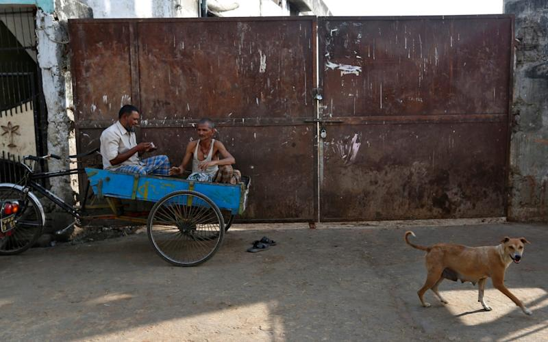 Bikanu Qureshi, 60, second left, who made living transporting meat rests on his cycle -cart in front of a slaughter house that was shutdown by authorities in Allahabad, India - Credit: Rajesh Kumar Singh/AP Photo