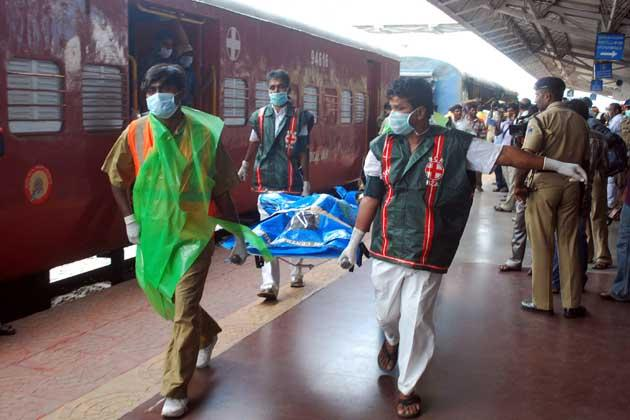 Medical staff carry away the body of a passenger killed in a train carriage fire, caused by an electrical short circuit killing at least 32, in Nellore on July 30, 2012. At least 32 people were killed July 30 when a fire ripped through a coach on an express train as it carried sleeping passengers to the southern Indian city of Chennai, officials said. AFP PHOTO/STR