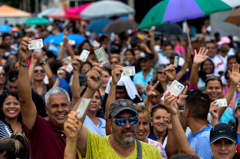 Venezuelans lining up to authenticate their signatures for a recall referendum before the National Electoral Council (CNE) show their ID cards in Maracay, Venezuela on June 23, 2016 (AFP Photo/Federico Parra)