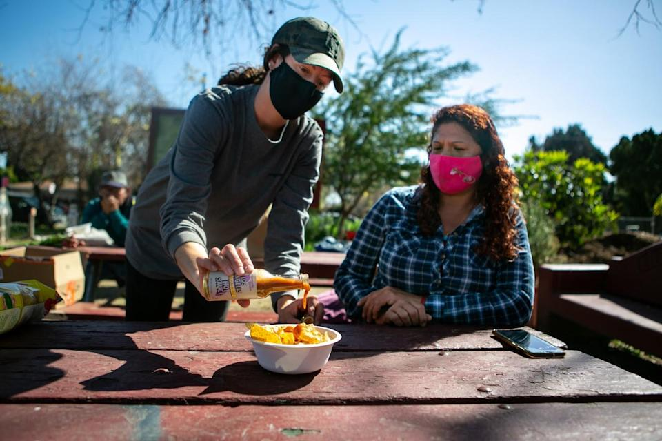 Elizabeth Christy, Program Manager at La Madera Community Garden, pours Small Axe Peppers sauce over some chips