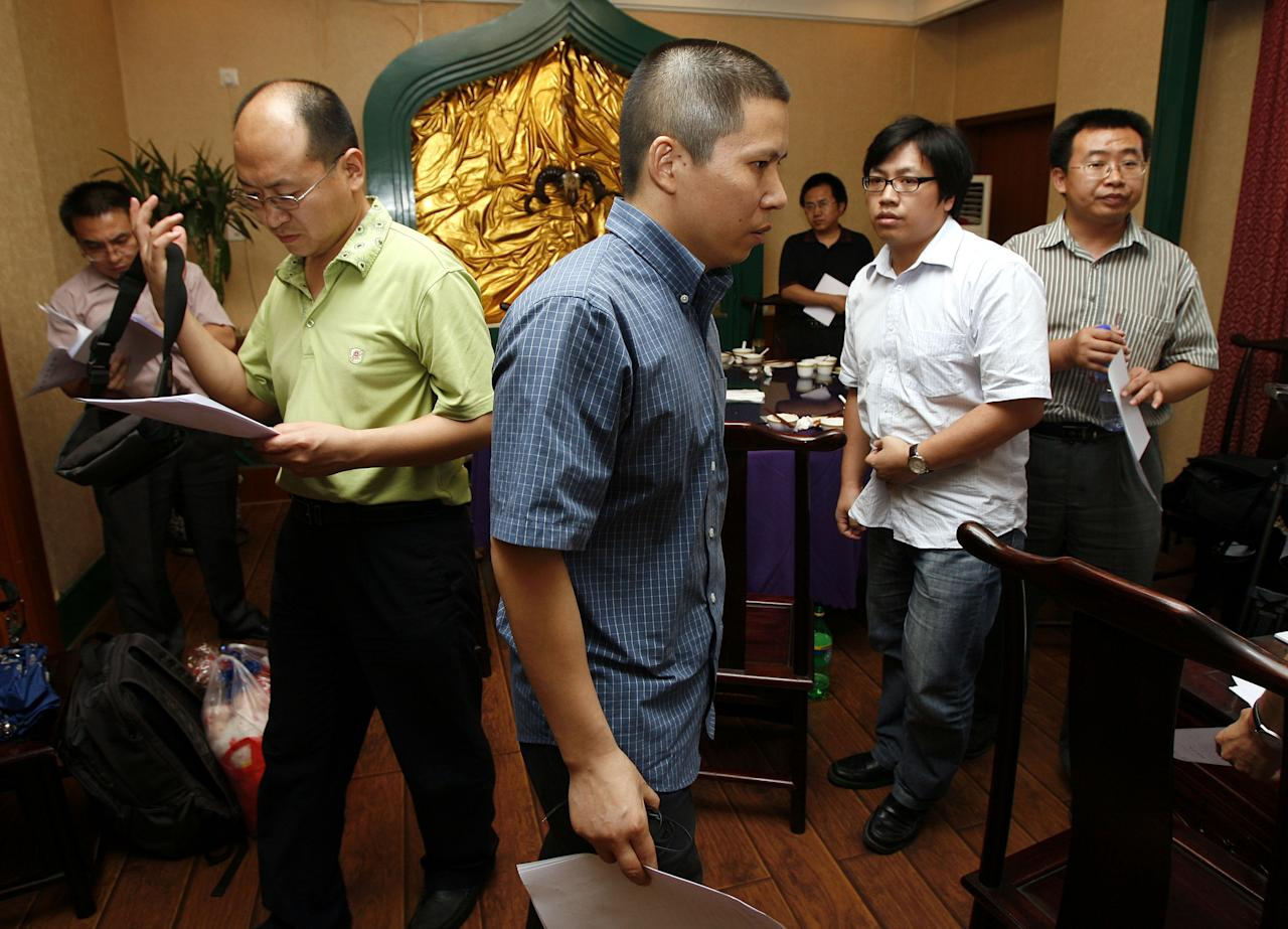FILE - In this July 17, 2009 file photo, legal scholar Xu Zhiyong, center, walks past Chinese lawyers, Jiang Tianyong, right, and Yang Huiwen, second left, after a meeting at a restaurant in Beijing, China. Detained Chinese legal activist Xu delivered a bold message from inside a Beijing jail, urging citizens to unite in pursuing democratic freedoms in a video posted online on Thursday, Aug. 8, 2013 that's sure to anger the authorities. (AP Photo/Greg Baker, File)
