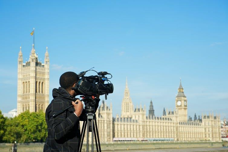 A man with a TV camera filming across the River Thames to Westminster Palace and the Houses of Parliament.