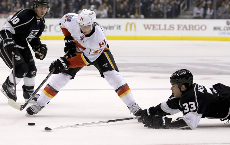 Los Angeles Kings defenseman Willie Mitchell, right, knocks the puck away from Calgary Flames center Mikael Backlund as Mike Richards looks on during the first period of an NHL hockey game in Los Angeles, Monday, Oct. 21, 2013. (AP Photo/Chris Carlson)