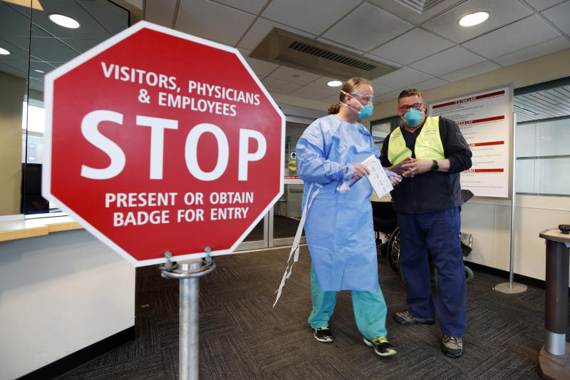Medical personnel discuss patients that had been admitted for testing for the coronavirus at the entrance Central Maine Medical Center Friday, March 13, 2020, in Lewiston, Maine. (Robert F. Bukaty/AP)