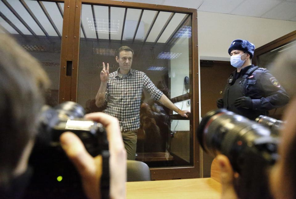 Russian opposition leader Alexei Navalny stands in a cage in the Babuskinsky District Court in Moscow, Russia, Saturday, Feb. 20, 2021. Two trials against Navalny are being held Moscow City Court one considering an appeal against his imprisonment in the embezzlement case and another announcing a verdict in the defamation case. (AP Photo/Alexander Zemlianichenko)