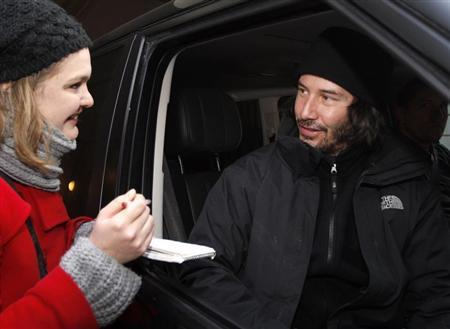 Reeves talks with a fan as he leaves his apartment in Budapest
