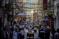 People walk along at a street, following the outbreak of the coronavirus disease (COVID-19), in Shanghai