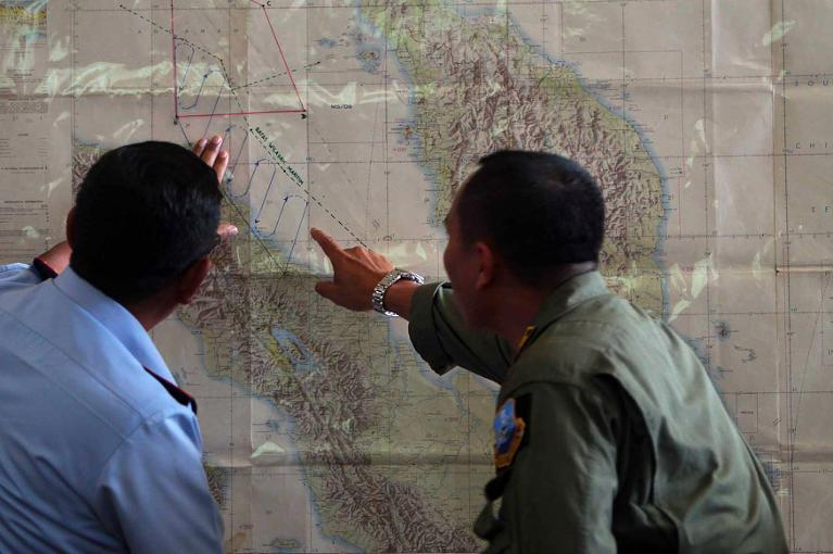 Indonesian Air Force officials at Medan city military base plot the Indonesian military search operation for the missing Malaysian Airlines flight MH370 on March 12, 2014