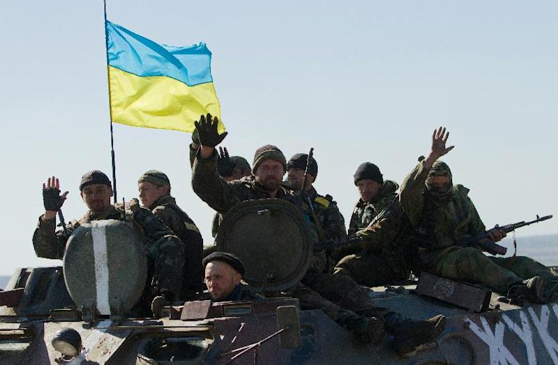 Ukrainian soldiers wave while patroling in an armored personnel carrier near Debaltseve on September 29, 2014 (AFP Photo/Anatolii Boiko)