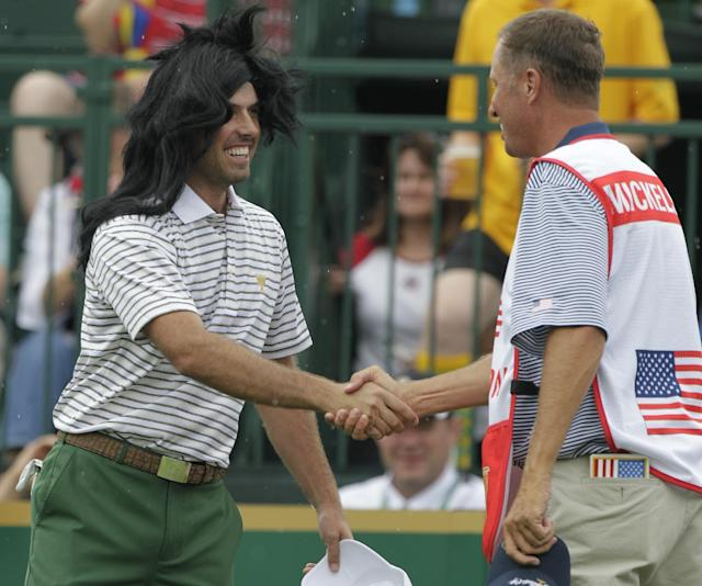 International team player Charl Schwartzel, left, of South Africa, wears a wig onto the first tee as he greets caddie Jim Mackay, who carries the bag for the United States' Phil Mickelson, before the start of the four-ball matches at the Presidents Cup golf tournament at Muirfield Village Golf Club Thursday, Oct. 3, 2013, in Dublin, Ohio. (AP Photo/Jay LaPrete)
