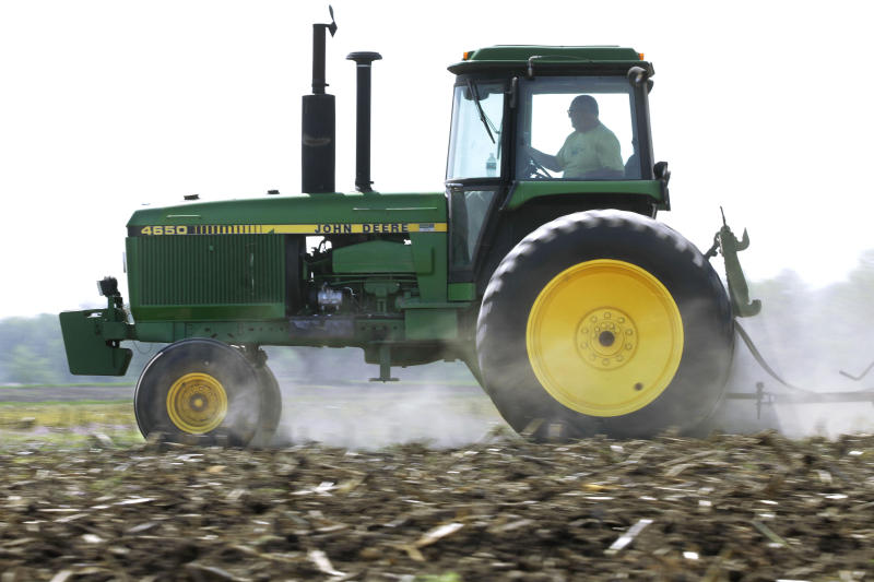 FILE - In this April 2, 2012 file photo, Derek Long uses a John Deere tractor to disk and cultivate a field in preparation for planting corn in Loami, Ill. John Deere & Co. reports quarterly earnings on Wednesday, Aug. 14, 2013. . (AP Photo/Seth Perlman, File)