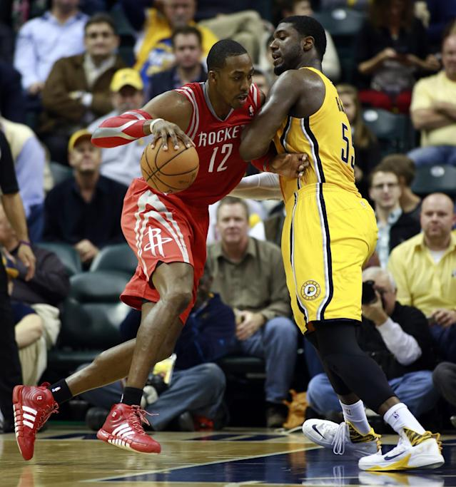 Houston Rockets center Dwight Howard (12) moves toward the basket whi2le guarded by Indiana Pacers center Roy Hibbert in the second half of an NBA basketball game in Indianapolis, Friday, Dec. 20, 2013. Indiana won 114-81. (AP Photo/R Brent Smith)