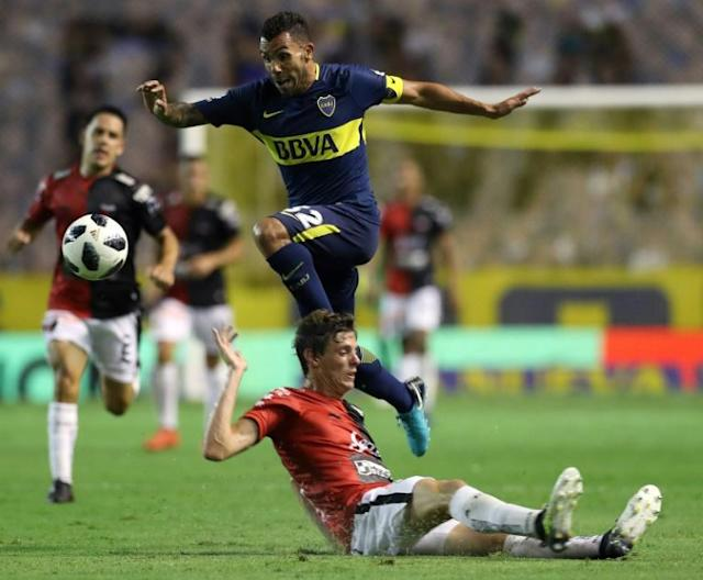 Boca Juniors' forward Carlos Tevez (C) jumps over Colon's defender German Conti during their Argentina First Division Superliga football match at La Bombonera stadium, in Buenos Aires, on January 27, 2018