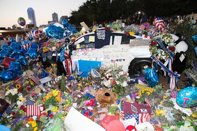 Flowers, cards, balloons, and candles pile on top of police vehicles outside the Police Headquarters in Dallas, Texas, on July 10, 2016 (AFP Photo/Laura Buckman)