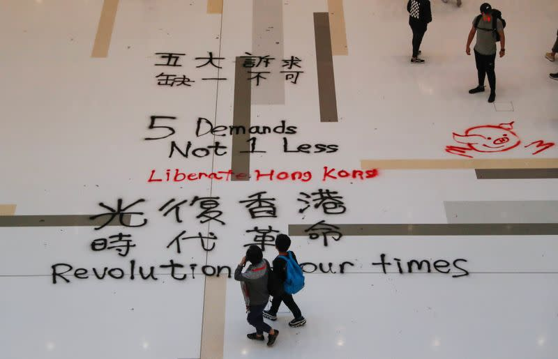 People walk past graffiti slogans written on the floor of a mall, in Hong Kong