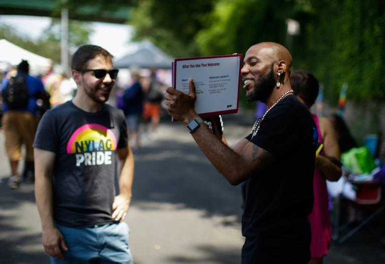 A man distributes information about an opioids prevention campaign during the Harlem Pride parade in New York on June 29, 2019 (AFP Photo/Kena Betancur)