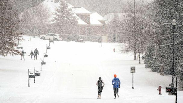 PHOTO: Joggers run down a street as a second winter storm in a week brings more snow, Feb. 18, 2021, in Nolensville, Tenn. (Mark Humphrey/AP)