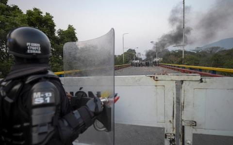 A Colombian police officer in Cucuta, Colombia, looks across the border at Venezuelan security forces - Credit: RAUL ARBOLEDA/AFP/Getty Images