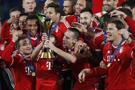 Germany's Bayern Munich Franck Ribery and Philipp Lahm hold the trophy as they celebrate with their team mates after winning their 2013 FIFA Club World Cup final match against Morocco's Raja Casablanca at Marrakech stadium