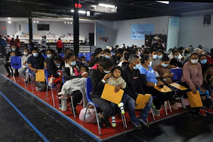 Asylum seekers holding manila envelopes sit in rows of chairs