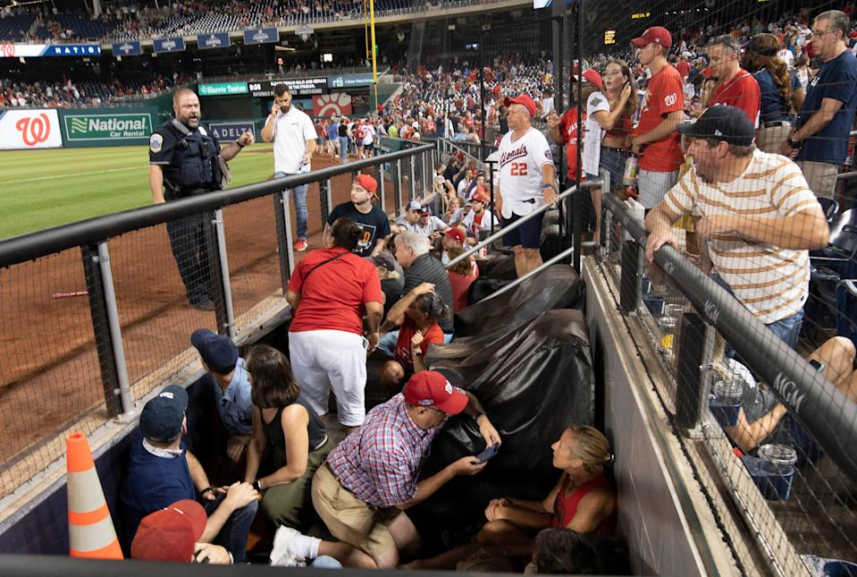Fans take cover after an apparent shooting occurred outside Washington's Nationals Park.
