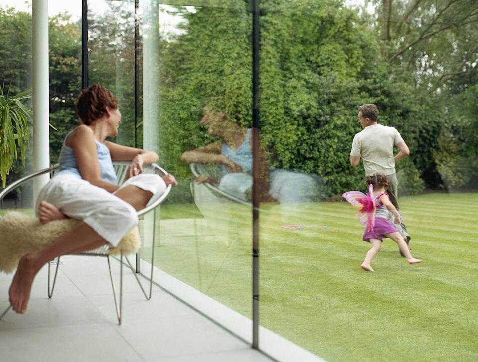 Woman looking out of window at father and daughter running in yard