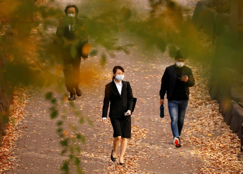 Passersby wearing protective face masks walk under autumn coloured leaves, amid the coronavirus disease (COVID-19) outbreak, in Tokyo