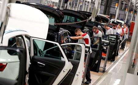 FILE PHOTO: Workers assemble vehicles on the assembly line of the SEAT car factory in Martorell, near Barcelona, Spain, October 31, 2018. REUTERS/Albert Gea/File Photo