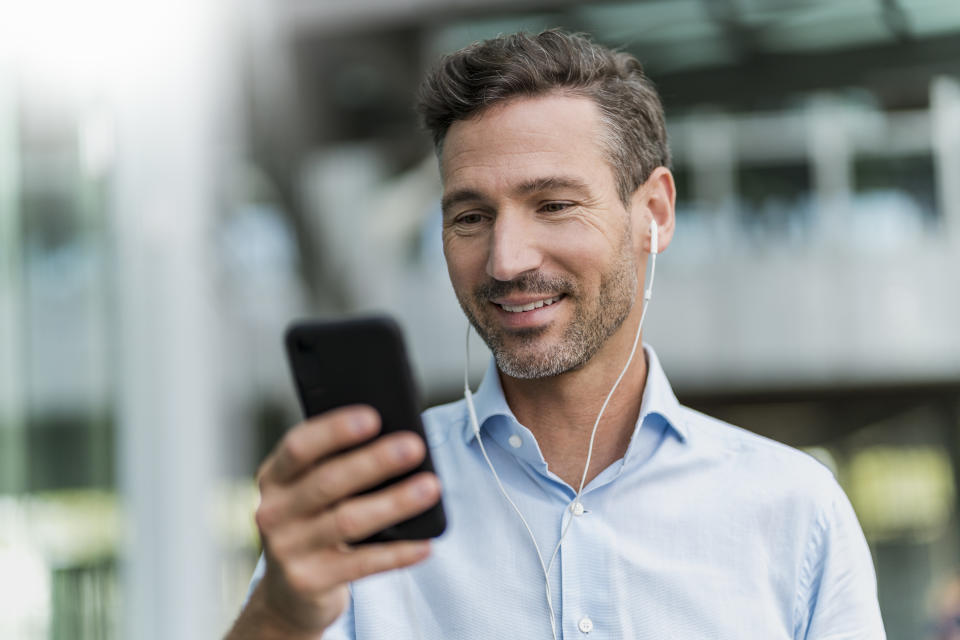 Smiling businessman with earphones and cell phone in the city